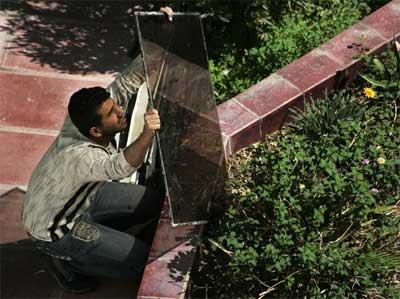 Một người ở Baghdad, Iraq chiêm ngưỡng nhật thực qua một tấm kính màu
