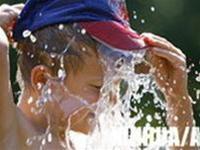"""Một bé trai đang """"giải nhiệt"""" từ vòi nước tại Berlin hôm 19-7"""