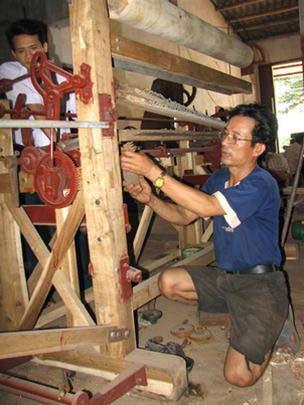 Anh Đặng Văn Nguyên đang lắp đặt máy dệt chiếu cho khách hàng.